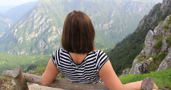 Girl sitting over high mountain view
