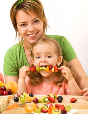 kid eating healthy snack with woman
