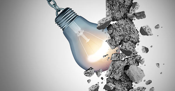 light build smashing through stone wall barrier to overcome creativity blockage
