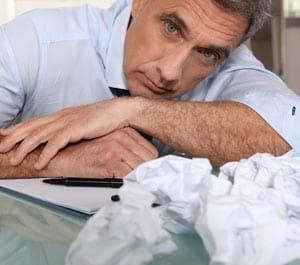 man staring at notepad having writer's block