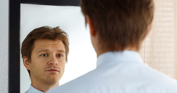 sad and unhappy man staring at self in mirror