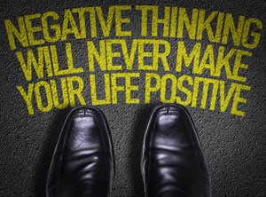 negative thinking quote with businessman's black shoes