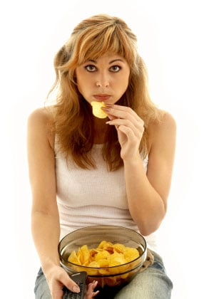 Girl eating chips looking depressed