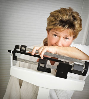 Mature woman leaning over weight scale looking disappointed