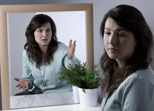 Woman turning her face away from her angry face in mirror - anger management concept