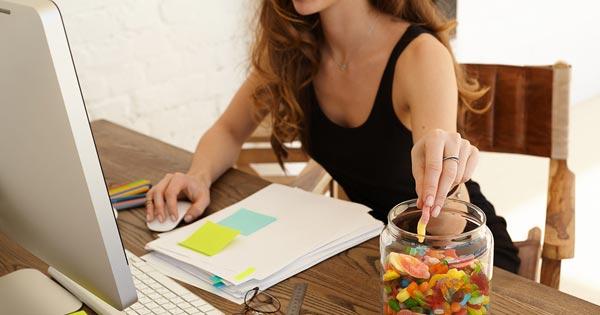 Girl grabbing sugar candy from jar at office as example of sugar and carb addiction