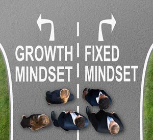 Diverging road one leading to growth mindset and other to fixed mindset