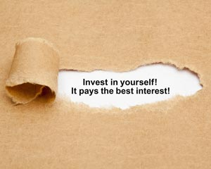 Invest in yourself message appearing behind a torn out paper window
