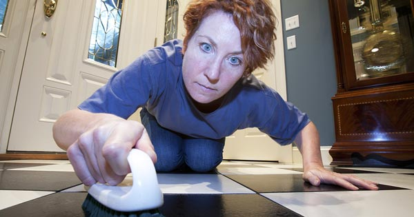 Woman with obsessive-compulsive order scrubbing a spotless floor