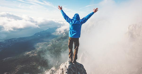 Man on mountain top with arms raised above head in success gesture