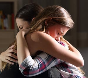 Grieving sad and crying friends embracing each other