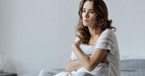 Sad and depressed young woman holding a pillow sitting on a bed
