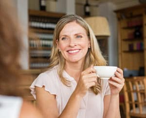 Mature woman chatting with friend in coffee shop