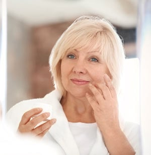Mature woman applying anti-aging cream