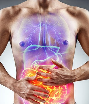 Man holding stomach experiencing gut pain