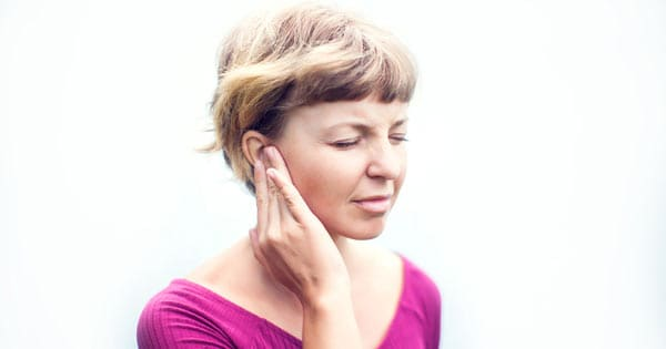 Tinnitus woman sufferer holding her ear with pain