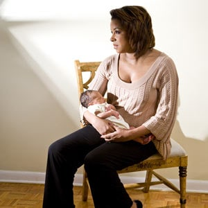 Woman feeling sad holding newborn baby