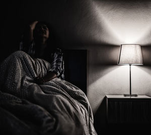 Woman in darkened room alone and depressed.