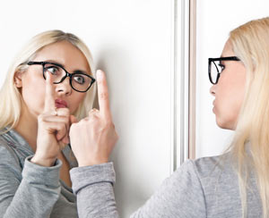 Woman talking to her reflection in a mirror