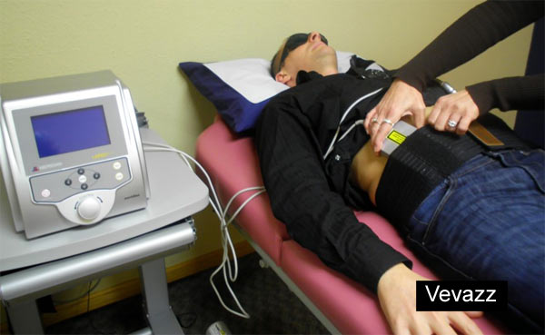 Man on masage table receiving laser-like lipo red-light therapy in office
