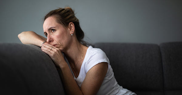 Depressed woman lounging on sofa looking stressed and anxious