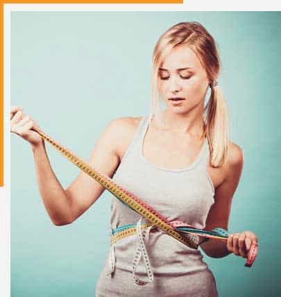 Image showing young woman holding tape measures around her waist depicting weight loss scenario